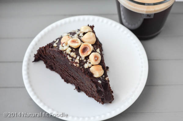 closeup horizontal view of one slice of hazelnut zucchini chocolate cake with a cup of coffee