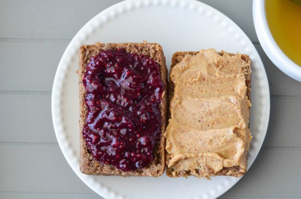 Overhead shot of Banana bread smothered in homemade almond butter and berry cherry chia seed jam.