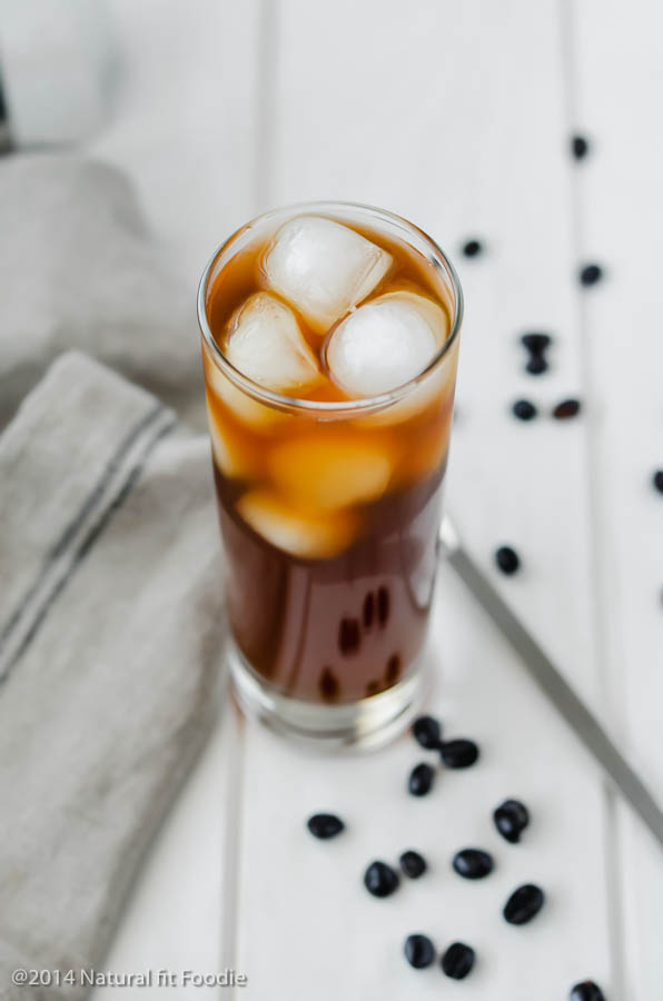 45 degree shot of kombucha coffee in a glass with ice on a white wooden backdrop.