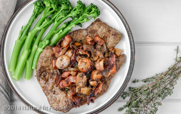 Overhead landscape shot of pan fried beef liver slices with onions,bacon and mushrooms on a white plate with broccolini on the side.