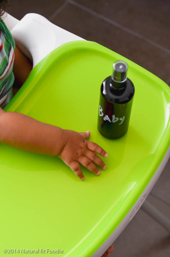 overhead shot of dark spray bottle with homemade highchair cleaner on top of clean high chair tray