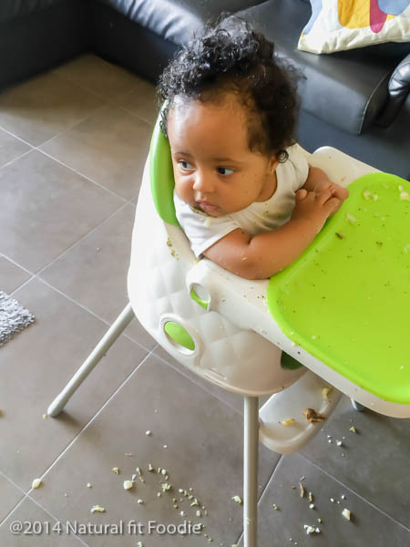 shot of baby sitting in highchair covered in baby food , food all over the floor