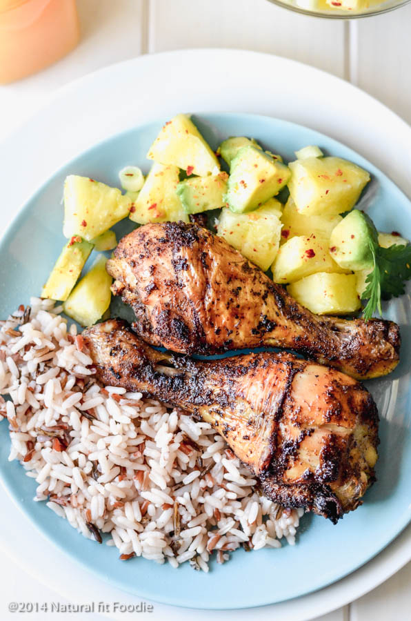 overhead view of Jamaican jerk chicken on a plate with wild rice and pineapple avocado salsa