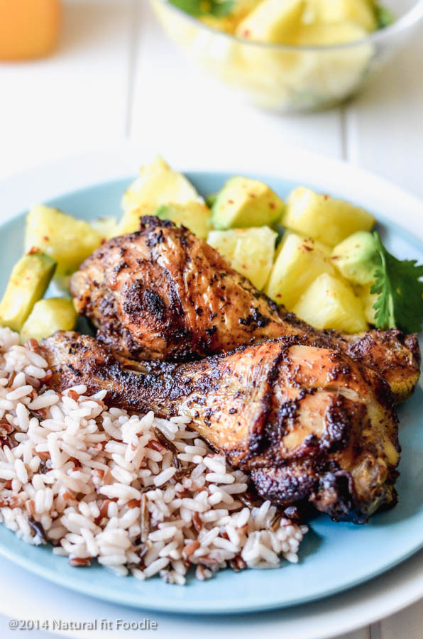 45 degree angle view of Jamaican jerk chicken on a plate with wild rice and pineapple avocado salsa