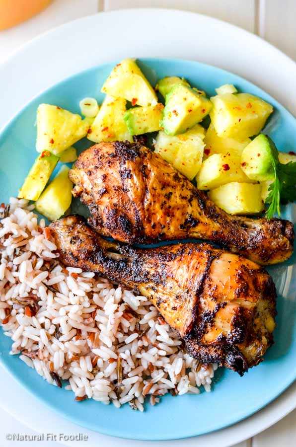 overhead view of baked jamaican chicken legs on blue plate with wild rice and pineapple avocado salsa